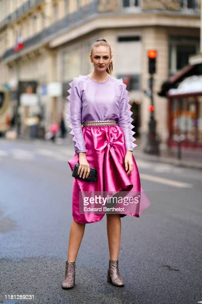 Julie Ianc wears a light purple longsleeves top, a studded belt, a lustrous hot pink flowing skirt, a glittering black clutch, glittering...