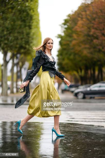 Julie Ianc wears a long gathered sleeves black frilly top, a lustrous yellow flowing elastic-waist skirt, blue pointy heels, outside Chanel, during...