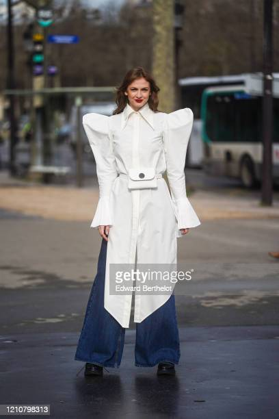 Julie Ianc wears a white oversized shirt with large shoulder pads, blue large denim jeans pants, a belt bag, black leather shoes, outside Chanel,...