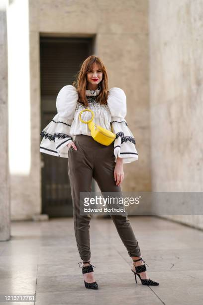 Julie Ianc wears a white ruffled an pleated top with puff shoulder parts khaki pants a yellow crossbody bag pointy shoes outside Elie Saab during...