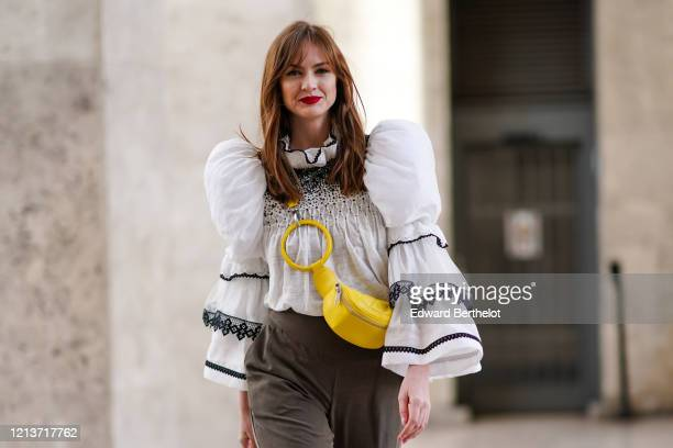Julie Ianc wears a white ruffled an pleated top with puff shoulder parts, khaki pants, a yellow crossbody bag, outside Elie Saab, during Paris...