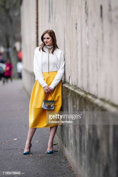 Julie Ianc wears a wite jacket a white turtleneck top a chain shaped golden necklace a yellow skirt a Furla bag blue shoes outside Valentino during...
