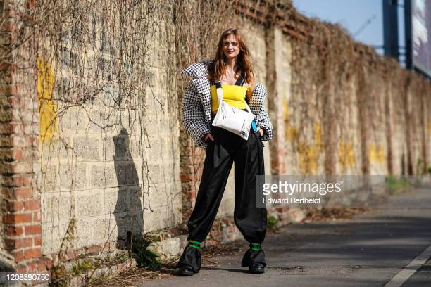 Julie Ianc wears a yellow off-shoulder top, a black and white houndstooth pattern printed large puffer jacket, a white bag, black lustrous pants,...