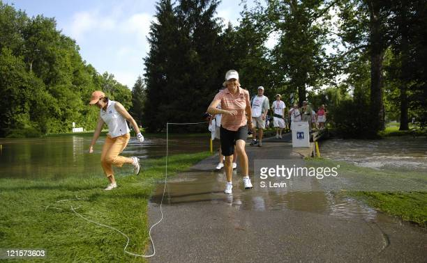 Julie Inkster and Liselotte Neumann jump over one of the many submerged paths during the first round of the Jamie Farr Owens Corning Classic at...