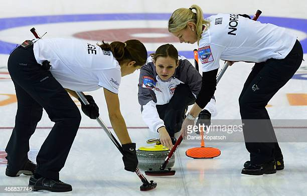 Julie Kjaer Molnar of Norway and team mate Camilla Holth sweep after Marianne Roervik throws a rock during the Olympic Qualification Tournament...