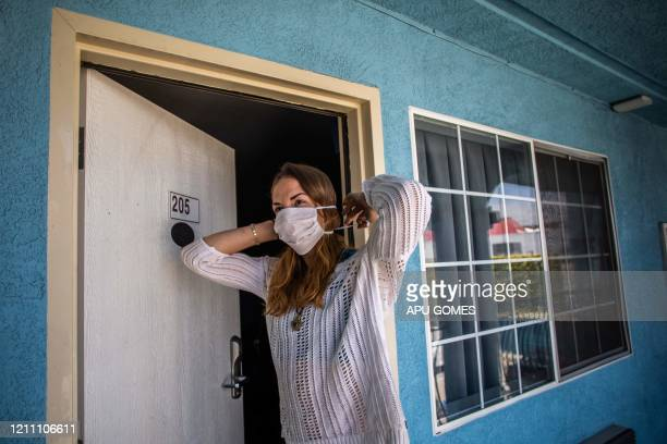 Julie Mariane puts her mask on a a motel room provided to homeless people by the NGO St Joseph Center as she gets ready to be transferred to a hotel...
