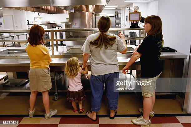 Julie Morris stands with her three daughters while awaiting extras after the dining hall closed at the Family Gateway homeless shelter on June 18,...