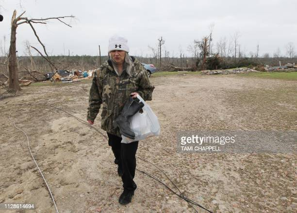 Julie Morrison carries belongings from her home after it was destroyed in a tornado in Beauregard Alabama on March 4 2019 Rescuers in Alabama were...