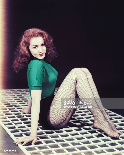 Julie Newmar US actress dancer and singer sitting on a white mat wearing a green shortsleeved woollen top and fishnet stockings circa 1955
