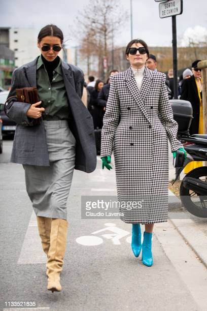 Julie Pelipas wearing a black turtleneck top military green shirt grey skirt grey blazer cream boots and brown bag and Irina Linovich wearing a long...