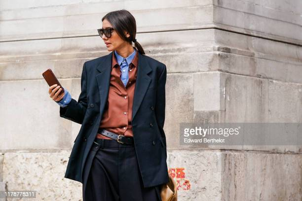 Julie Pelipas wears sunglasses, a blue shirt, a rust-color shirt, a dark grey oversized double-breasted jacket, dark grey oversized pants, a black...