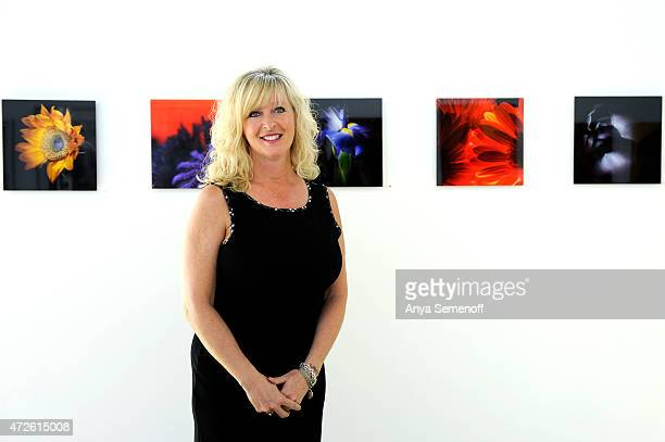 Julie Powell poses for a portrait alongside some of her photographs hanging at Valkarie Gallery on April 30 in Lakewood Colorado Powell started...