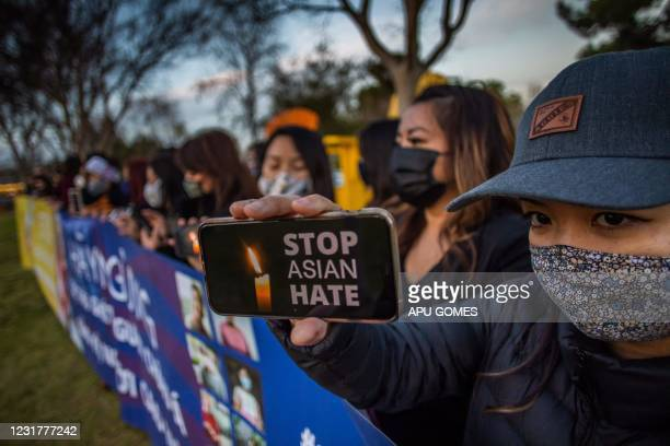 Julie Tran holds her phone during a candlelight vigil in Garden Grove, California, on March 17, 2021 to unite against the recent spate of violence...