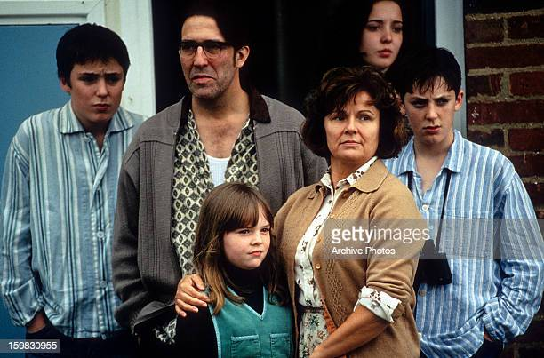 Julie Walters and Ciarán Hinds stand with their family in a scene from the film 'Titanic Town' 1998