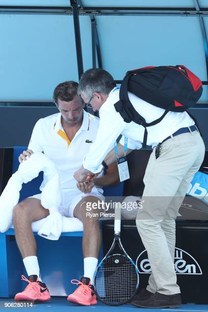 Julien Benneteau of France receives medical attention in his second round match against David Goffin of Belgium on day four of the 2018 Australian...