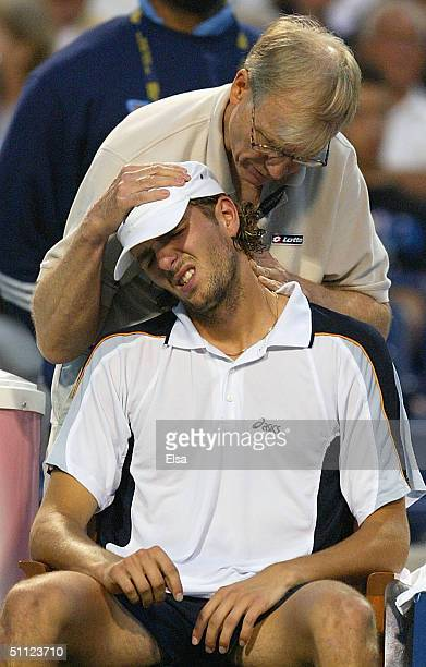 Julien Benneteau of France receives treatment by a medical trainer in the second set against Andy Roddick of the USA during the Tennis Masters Canada...