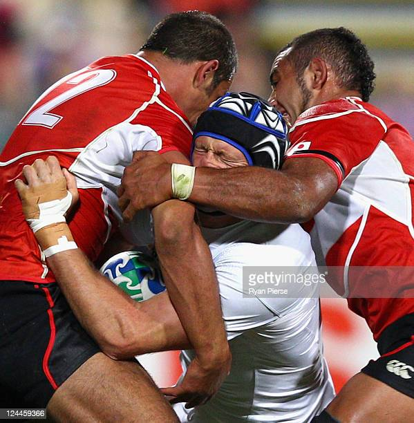 Julien Bonnaire of France is tackled by Ryan Nicholas and Michael Leitch of Japan during the IRB 2011 Rugby World Cup Pool A match between France and...