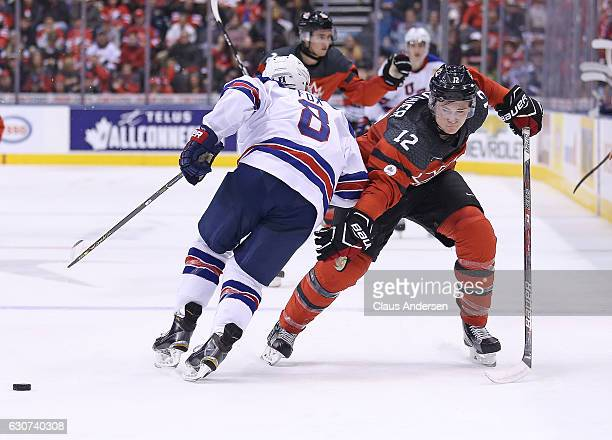 Julien Gauthier of Team Canada side steps a hit by Adam Fox of Team USA during a preliminary round game in the 2017 IIHF World Junior Hockey...