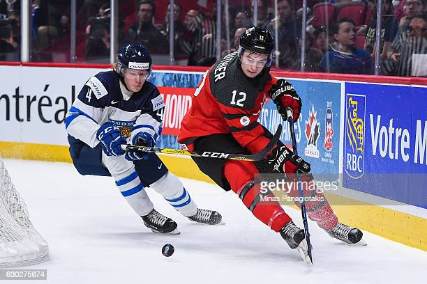 Julien Gauthier of Team Canada skates the puck against Robin Salo of Team Finland during the IIHF exhibition game at the Bell Centre on December 19...