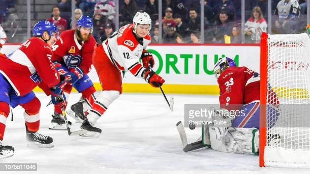 Julien Gauthier of the Charlotte Checkers tries to score on Connor Lacouvee of the Laval Rocket while Brett Lernout of the Laval Rocket and David...