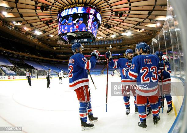 Julien Gauthier of the New York Rangers high-fives Brendan Lemieux and Adam Fox as they celebrate a goal scored by teammate Kevin Rooney during the...