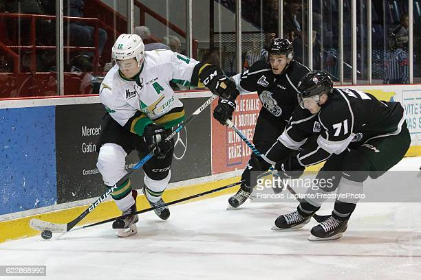 Julien Gauthier of the Vald'Or Foreurs controls the puck against Nicolas Meloche and /Matthew Thorpe of the Gatineau Olympiques on November 12 2016...