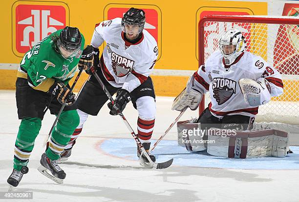 Julien Gauthier of the Val'Dor Foreurs looks to control a puck in front of Ben Harpur and Justin Nichols of the Guelph Storm in Game Four of the 2014...