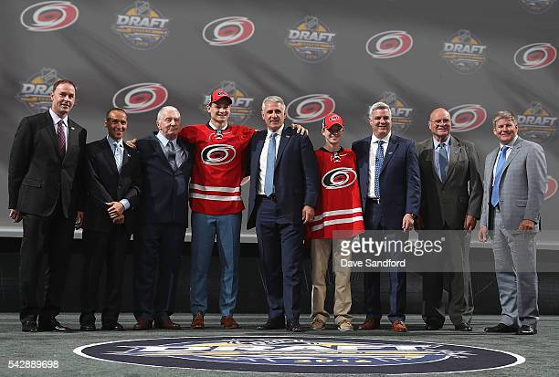 Julien Gauthier selected 21st overall by the Carolina Hurricanes poses onstage for a photo with the Carolina Hurricanes team personnel during round...