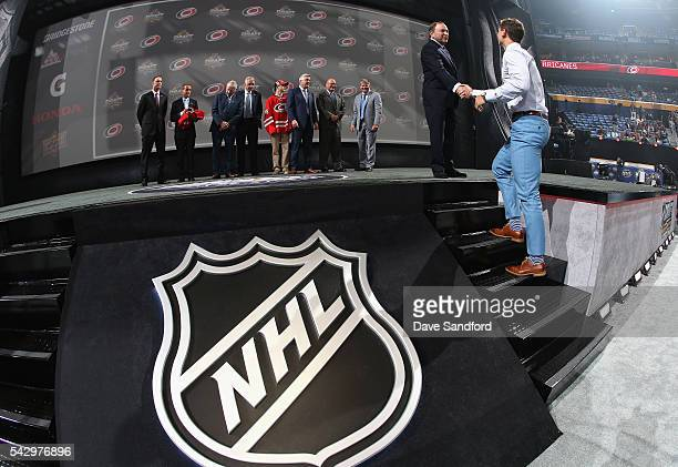Julien Gauthier shakes hands with NHL commissioner Gary Bettman after being selected 21st overall by the Carolina Hurricanes during round one of the...