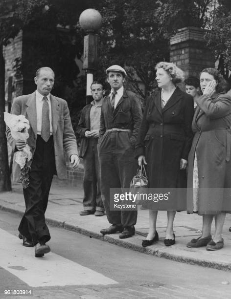 Julien Neilson the brother of convicted murderer Ruth Ellis arrives at Holloway Prison in London with a bunch of white carnations on the day of his...