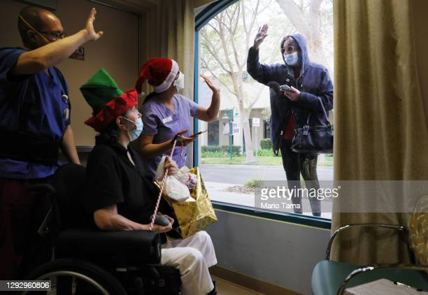 Juliet Babayan waves goodbye to her sister Violet Bonyad and caregivers after bringing a present for Violet and visiting through a window at the...