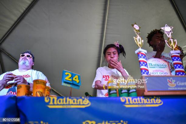 Juliet Lee of Germantown MD center competes on stage in the 2017 Hot Dog Eating Contest qualifier on Saturday June 24 in Washington DC The top male...