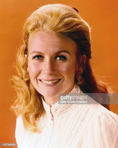 Juliet Mills British actress wearing a highneck white lacetrim blouse smiling in a studio portrait against an orange background circa 1965