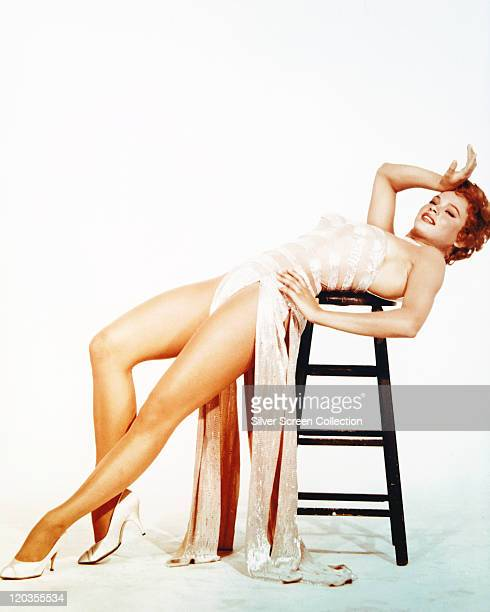 Juliet Prowse South African dancer wearing a long white dress with a split skirt which exposes her legs as she leans back over a stool in a studio...