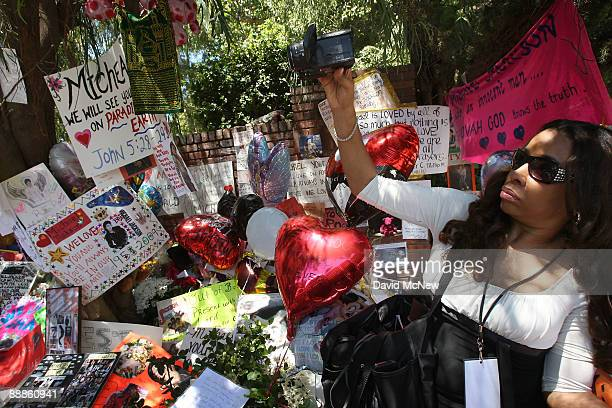Juliette Hagerman takes video for a Nigerian television station at a makeshift memorial outside the Jackson family home as Los Angeles prepares for...