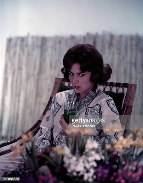 Juliette Mayniel Poses In Studio. Portrait studio de Juliette MAYNIEL, assise dans un fauteuil en osier, sirotant un verre de menthe, au premier plan...