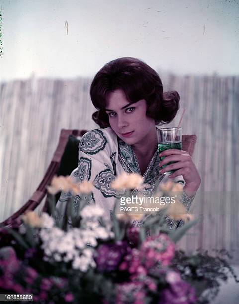 Juliette Mayniel Poses In Studio. Portrait studio de Juliette MAYNIEL, assise dans un fauteuil en osier, tenant un verre de menthe, au premier plan...