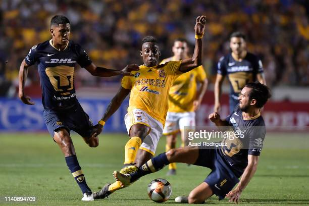 Julián Quiñones of Tigres fights for the ball with Jeison Angulo and Luis Quintana of Pumas during the 23th round match between Tigres UANL and Pumas...