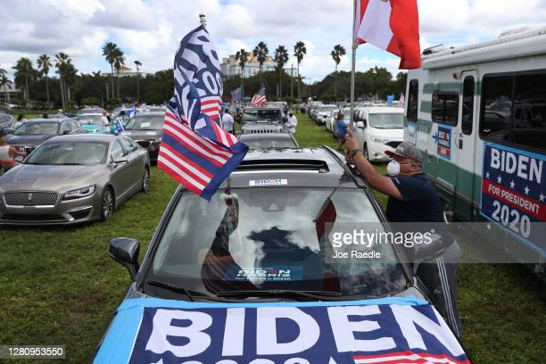 Julio Acosta places flags on his vehicle as he shows support for Democratic presidential nominee Joe Biden during a Worker Caravan for Biden event on...