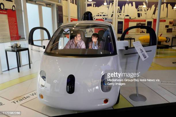 Julio Alvarez, at left, and Sandra Galvez, visiting from Miami, Florida, sit in a self-driving Google car at the Computer History Museum Thursday,...