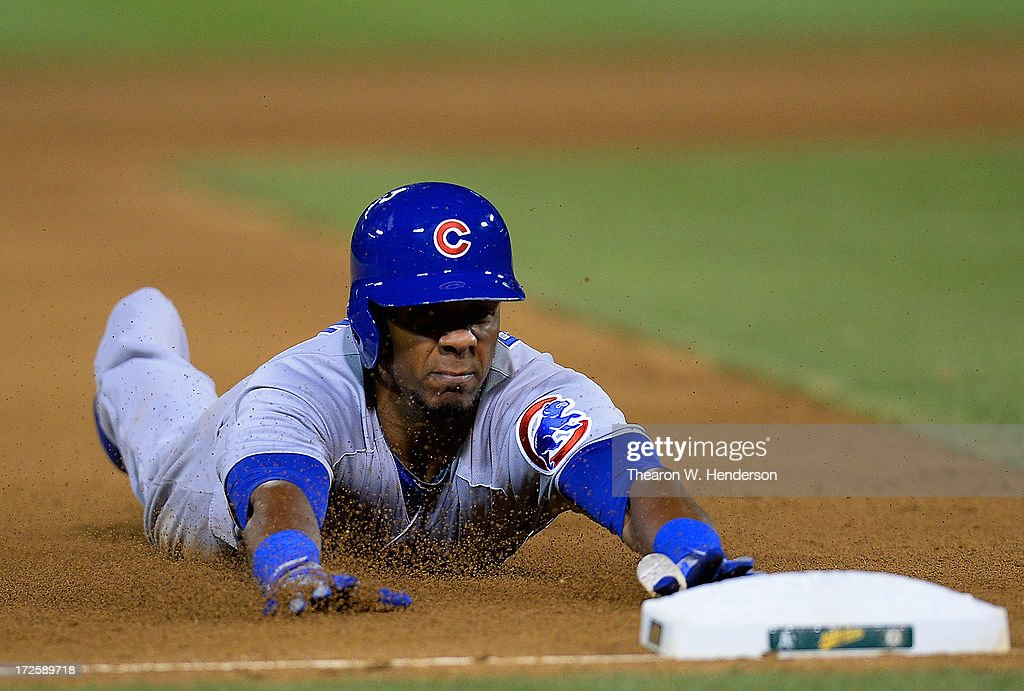 Julio Borbon #20 of the Chicago Cubs dives into third base with a triple in the seventh inning against the Oakland Athletics at O.co Coliseum on July 3, 2013 in Oakland, California.