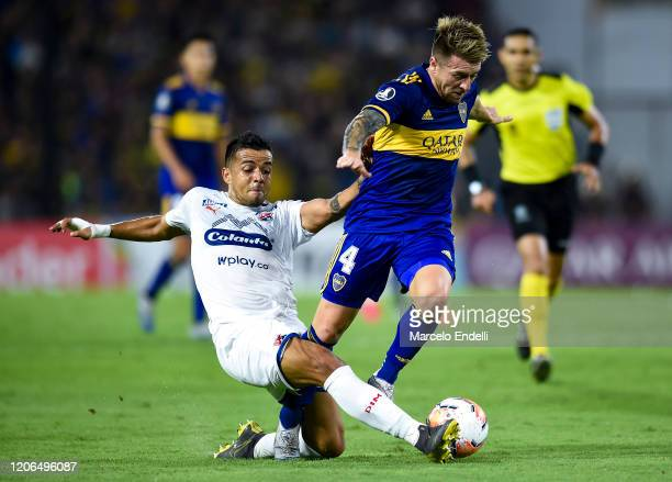 Julio Buffarini of Boca Juniors fights for the ball with Francisco Flores of Deportivo Independiente Medellin during a Group H match between Boca...