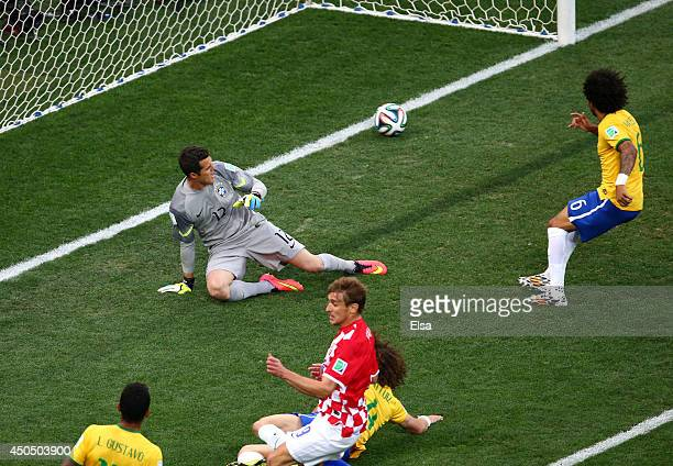 Julio Cesar and Marcelo of Brazil watch as a deflected shot goes in during the 2014 FIFA World Cup Brazil Group A match between Brazil and Croatia at...