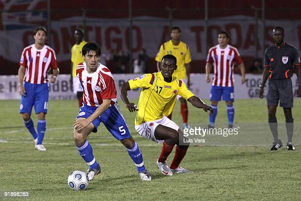 Julio Cesar Caceres of Paraguay vies for the ball with Jackson Martinez of Colombia during their match as part of the 2010 FIFA World Cup Qualifier...