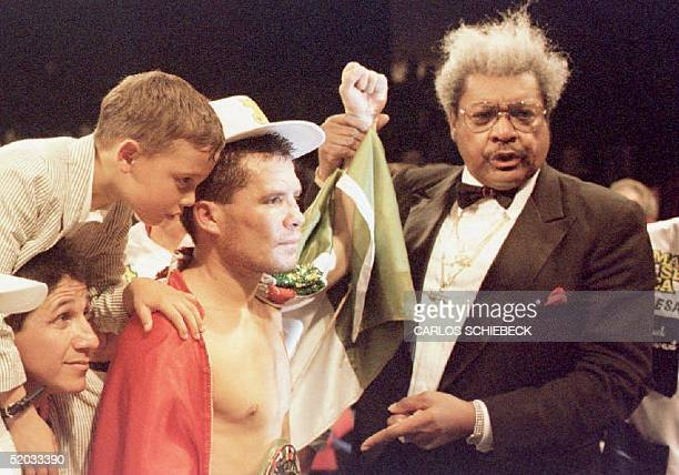 Julio Cesar Chavez of Mexico is surrounded by his son Julio Jr and promoter Don King after judges awarded Chavez a victory in his WBC Super...