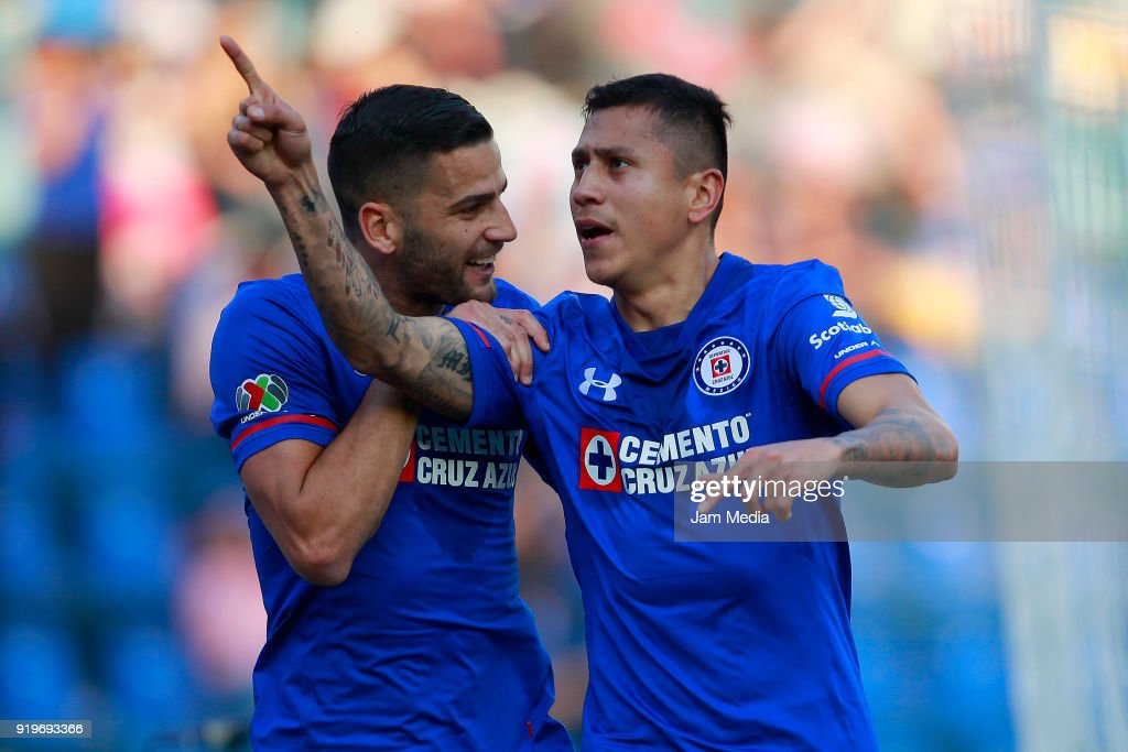 Julio Cesar Dominguez of Cruz Azul celebrates with teammate Martín Cauteruccio after scoring the first goal of his team with teammate Edgar Mendez during the 8th round match between Cruz Azul and Puebla as part of the Torneo Clausura 2018 Liga MX at Azul Stadium on February 17, 2018 in Mexico City, Mexico.