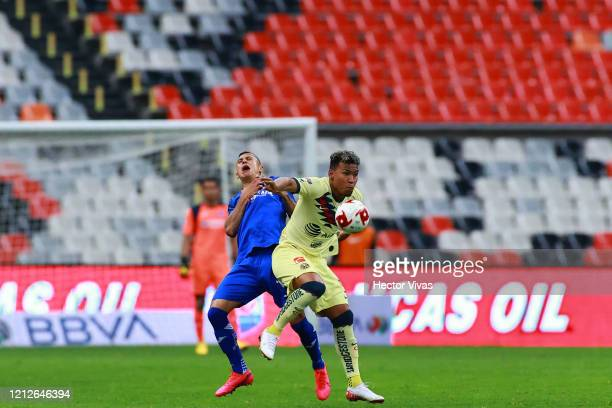 Julio Dominguez of Cruz Azul struggles for the ball against Roger Martínez of America during the 10th round match between America and Cruz Azul as...