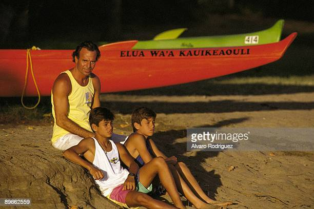 Julio Iglesias next to his sons Enrique and Julio Jose in Hawai Sat down in the beach next to a boat
