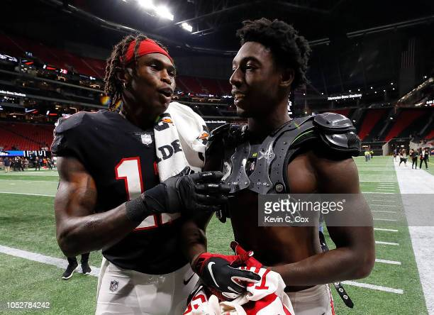 Julio Jones and Calvin Ridley walk off the field after their 2320 win over the New York Giants at MercedesBenz Stadium on October 22 2018 in Atlanta...