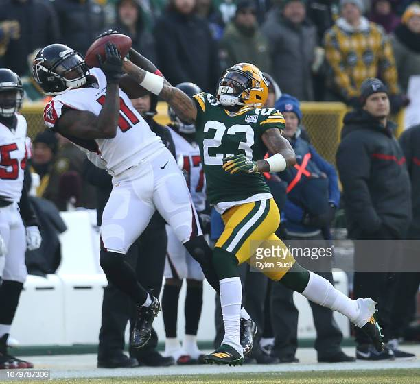 Julio Jones of the Atlanta Falcons catches a pass in front of Jaire Alexander of the Green Bay Packers during the first half of a game at Lambeau...